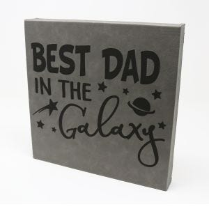 Gray engraved leather wall art with Best Dad in the Galaxy design on the front.