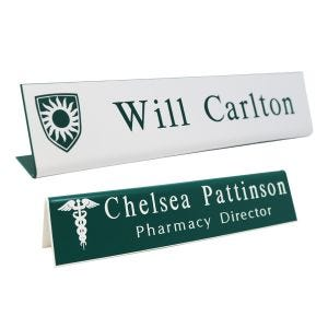 L-shaped name plates with engraved logo and text lines. White background with green engraving and green background with white engraving.
