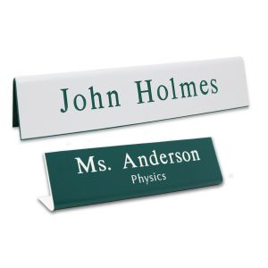 L-shaped name plates with engraved text lines. White background with green engraving and green background with white engraving.