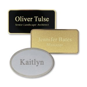 Rectangle and oval shaped black, gold, and silver metal name tags with engraved text on a matte metal face with shiny metallic underneath.