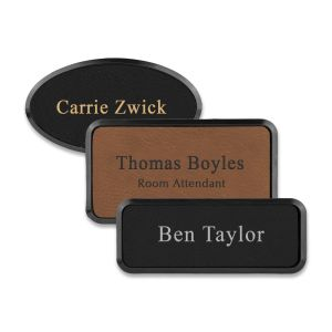 Framed rectangle and oval black and brown leather name tags with engraved lines of text