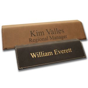 Leatherette desk wedges with lines of text. Brown leather with dark brown laser engraving and black leather with gold laser engraving.
