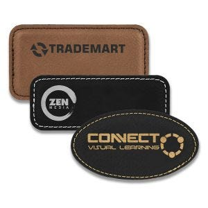Rectangle and oval brown and black leatherette name tags with engraved logos.