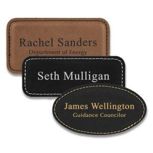 Rectangle and oval shaped black and brown leather name tags with engraved lines of text.